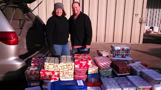 Rodney and Jana Mullenix of Flights For Christ standing next to several boxes that were collected.
